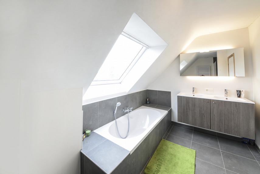Badkamer met bad en badkamermeubel in nieuwbouwwoning