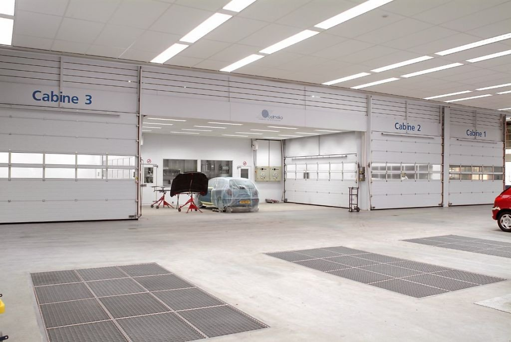 Auto refinish shop with sideways transport between the paint booths