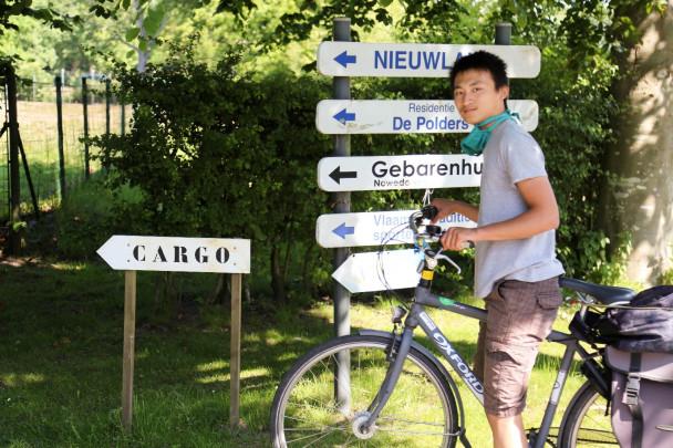 Jonge man met mondmasker poseert met fiets voor verkeersborden