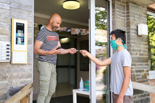 Begeleider ontvang sleutelhanger van jonge man met mondmasker