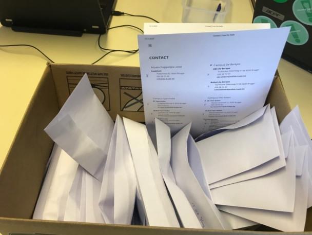 Gevulde witte enveloppen in kartonnen doos met contactlijst