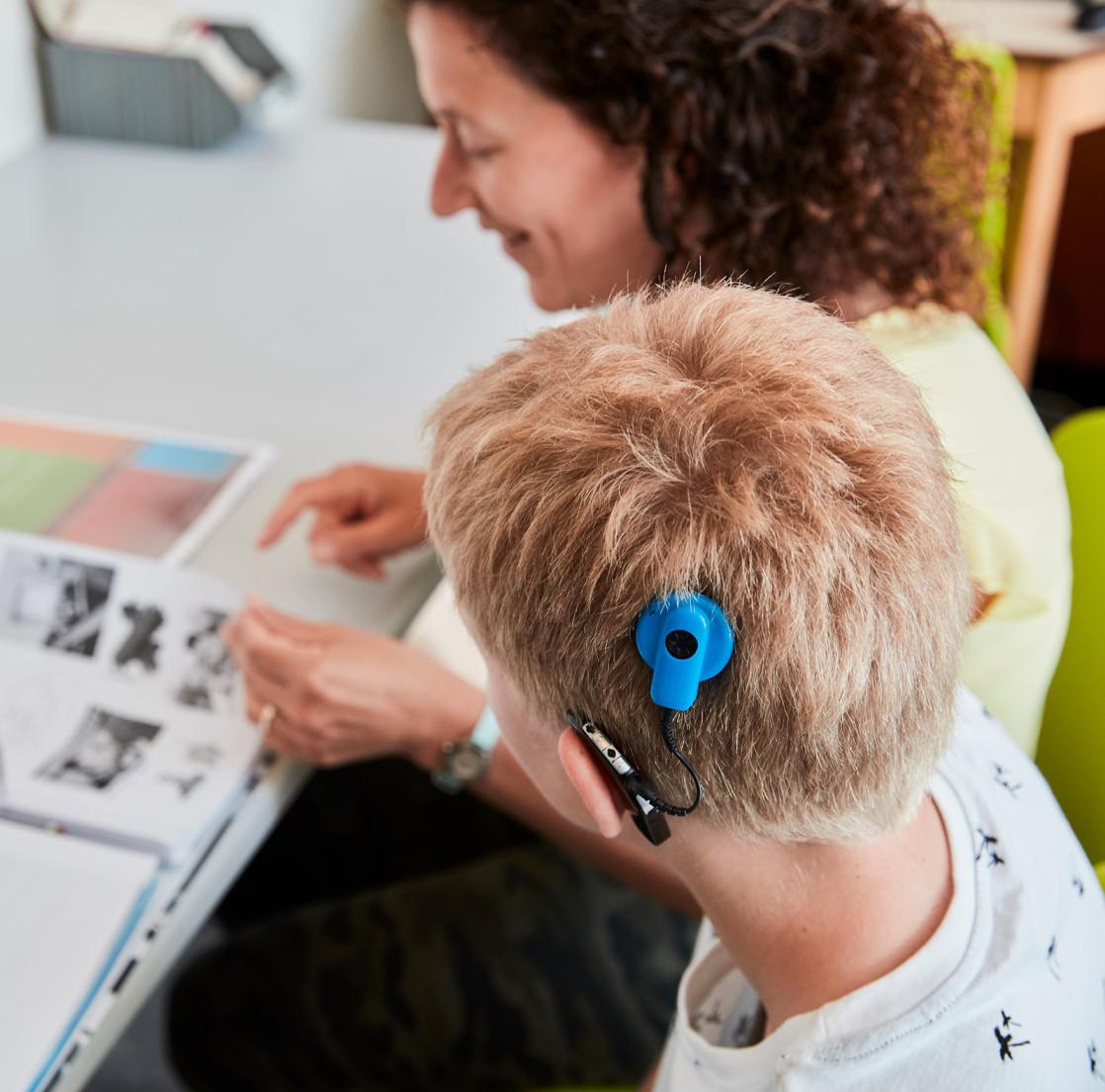 Jongen met hoorapparaat leest samen met juffrouw boek