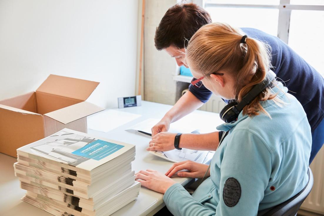 Begeleidster helpt vrouw met blauwe trui en bril uitnodigingen versturen