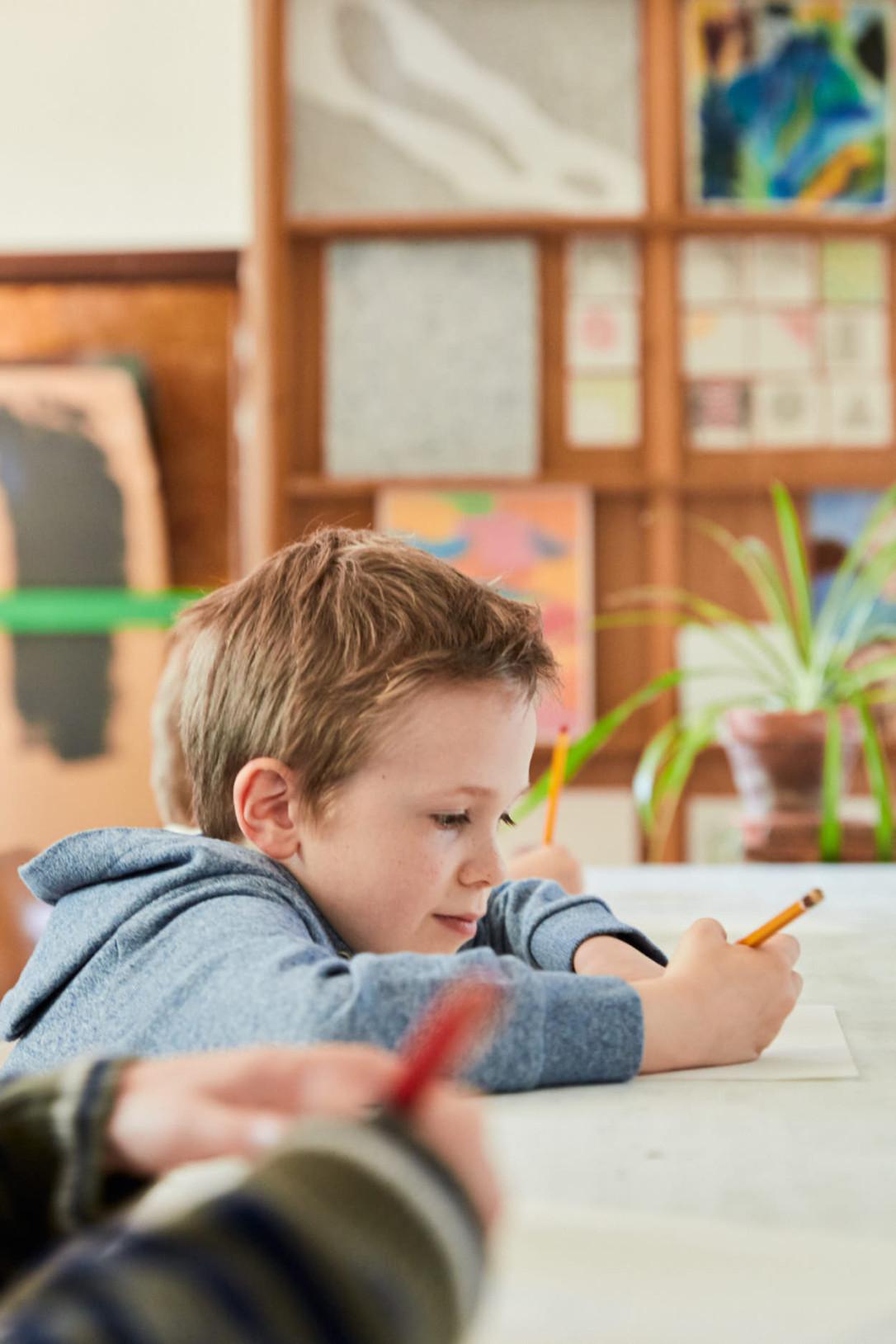 Drie jongens aan het opletten en noteren in de klas