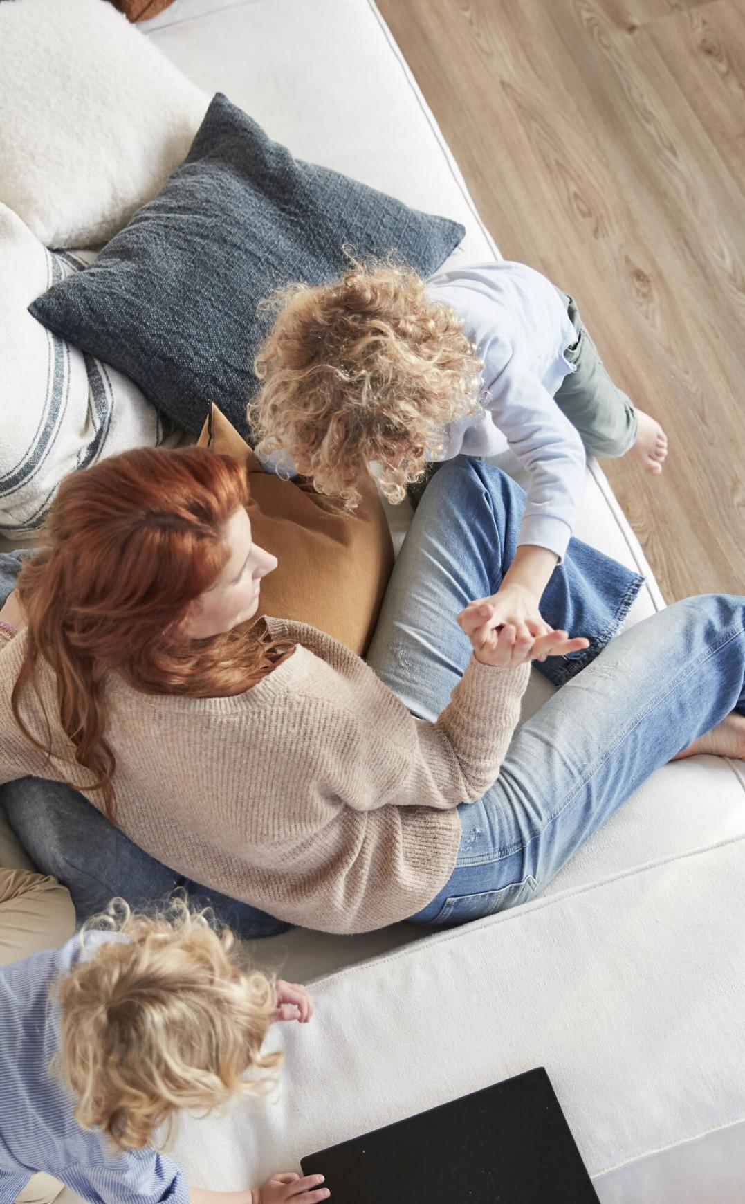 Une mère joue avec ses enfants dans un canapé